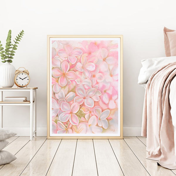 large watercolour of a pink lilic flower head propper up against a wall next to a bed and bedside table