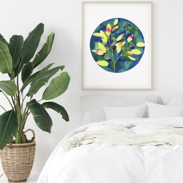 watercolour of a yellow eucalyptus plant with a blue colourful background hanging above a white bed and a plant
