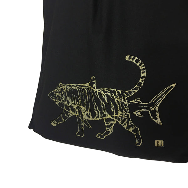 close up detail of a black tote bag print which is a gold outline of a shark and tiger superimposed on it