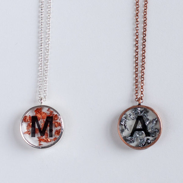 two necklace pendants hanging one is silver plated with metallic foil and the letter M and the other copper plated with silver foil and the letter A