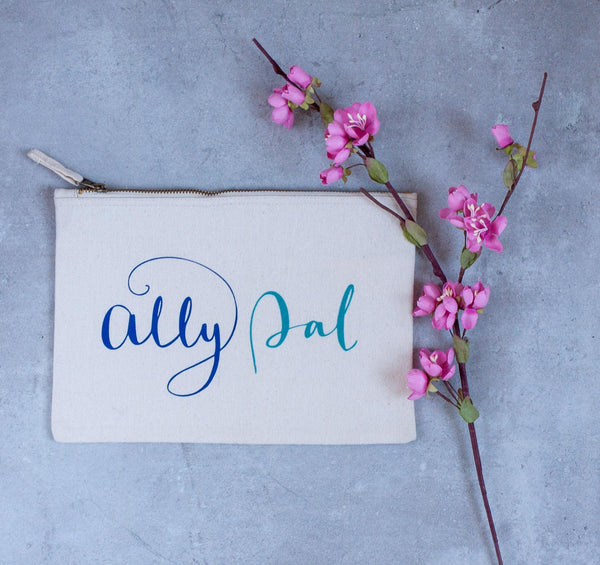 natural coloured baby child nappy pouch bag with the words ally pally printed on it in light and dark blue lying on a concrete floor next to a pink flower