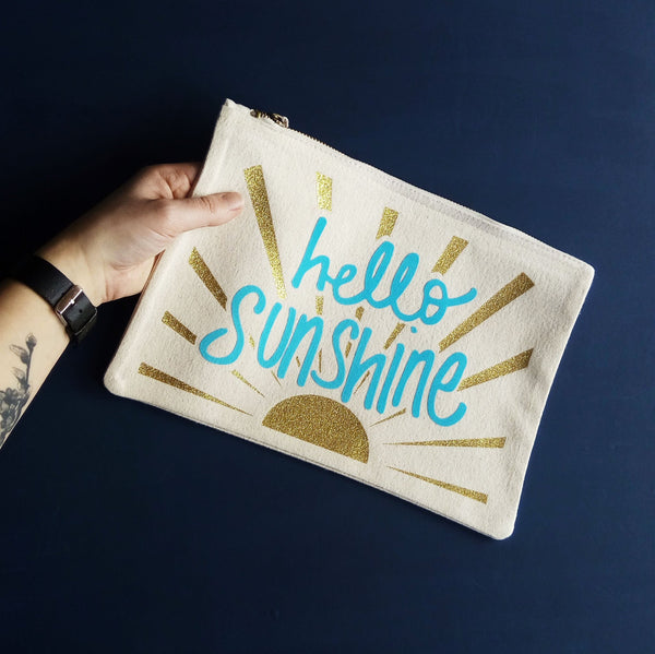 a hand holding a natural coloured baby child nappy pouch bag with the words hello sunshine printed in blue on itand gold sunrays decorating the bag