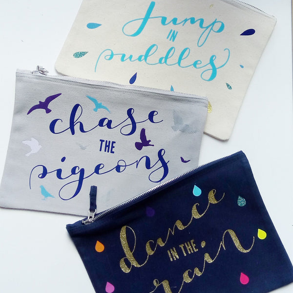 three different baby child colour nappy pouch bags lying next to each other with different words on them dance in the rain jump in puddles and chase the pigeons