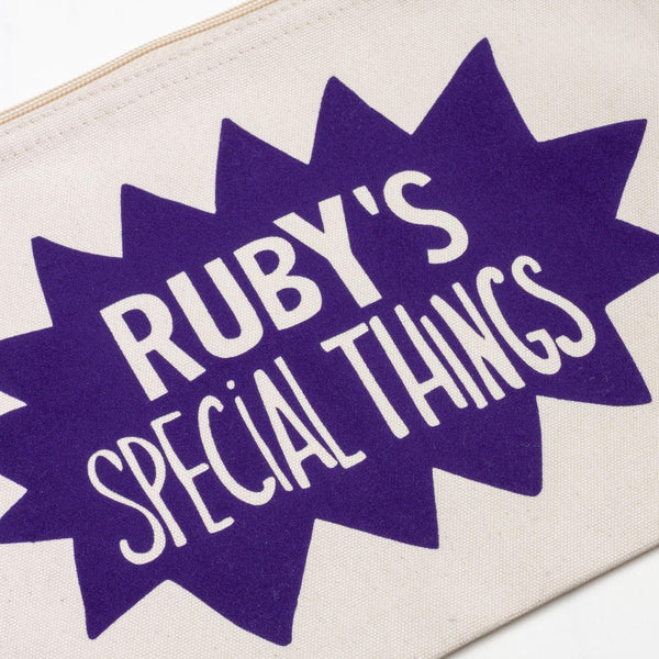 close up detail of a baby child natural coloured nappy pouch bag for baby and children with the words rubys things printed on it in a fun purple splat