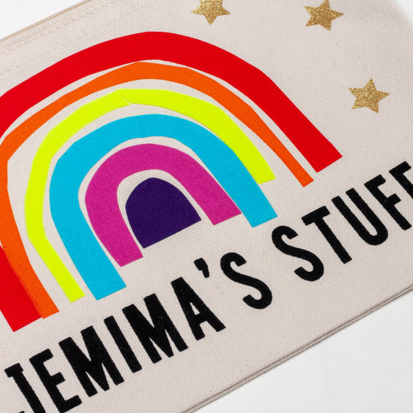 close up detail of a natural coloured nappy pouch bag for baby and children with a colourful rainbow printed on it and the words jeminas stuff printed in black with gold stars decorating it