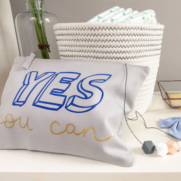 blue baby child nappy pouch bag with the words yes you can printed on it in dark blue and gold propped up on a shelf surrounded by nappies and a baby teething necklace
