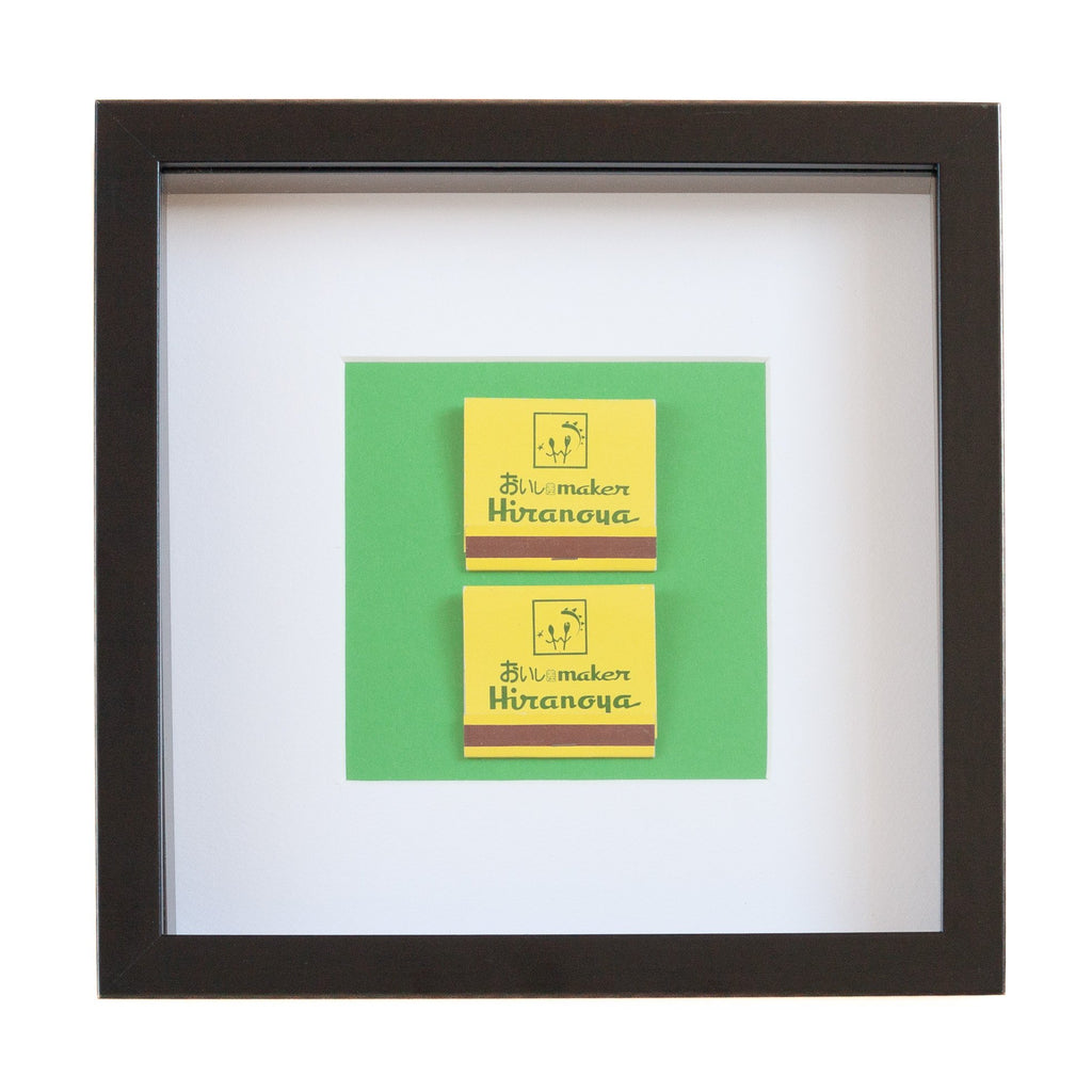 two japanese vintage yellow match boxes mounted on a green background in a picture frame