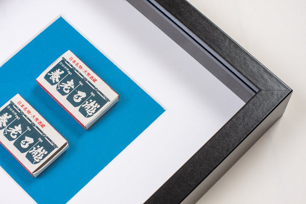 detail of two japanese vintage match boxes mounted on a blue background in a picture frame