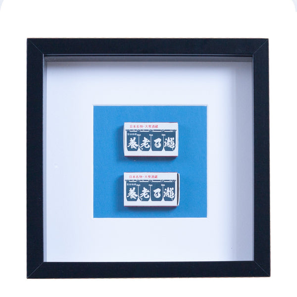 two japanese vintage match boxes mounted on a blue background in a picture frame
