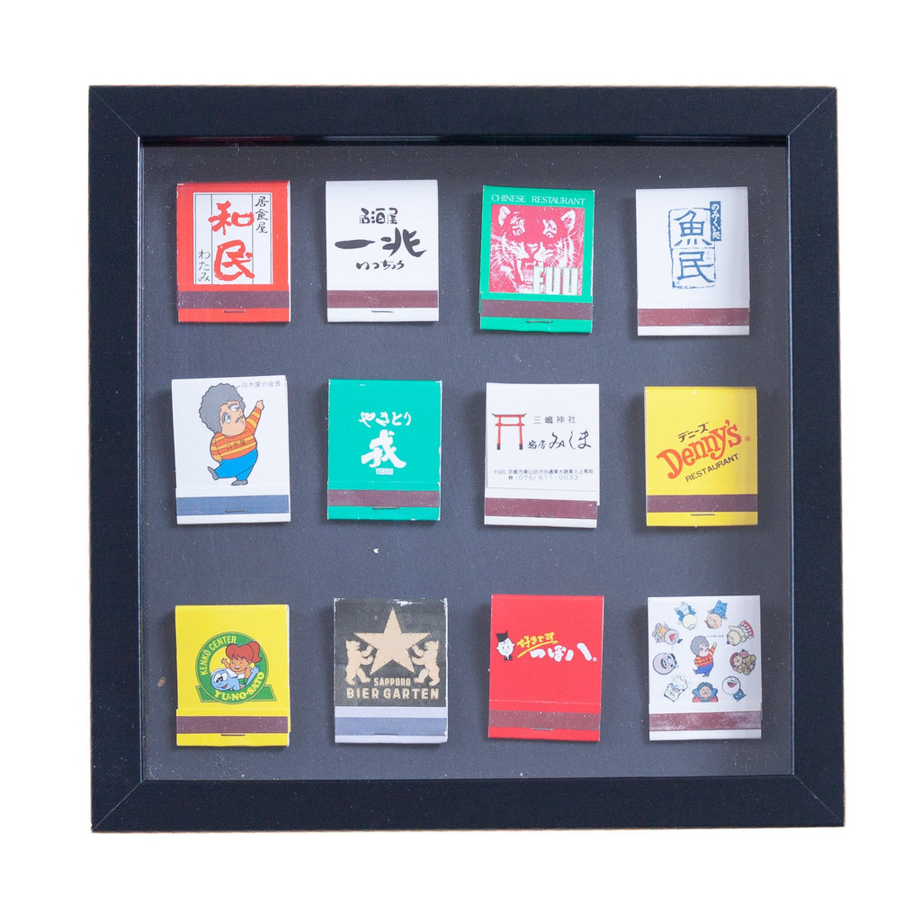 twelve japanese vintage match boxes mounted on a grey background in a picture frame