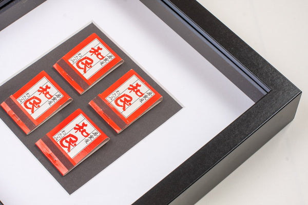 detail of four red japanese vintage matchboxes mounted on a grey background all framed
