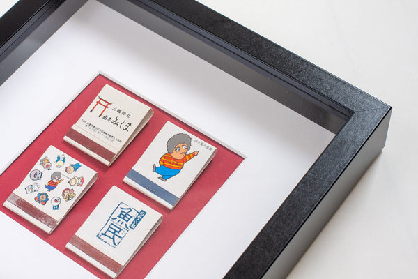 detail of four japanese vintage matchboxes mounted on a red background all framed