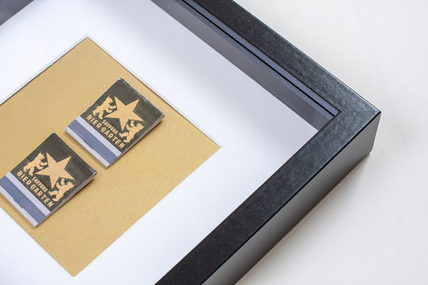 detail of two japanese vintage match boxes mounted on a gold background in a picture frame