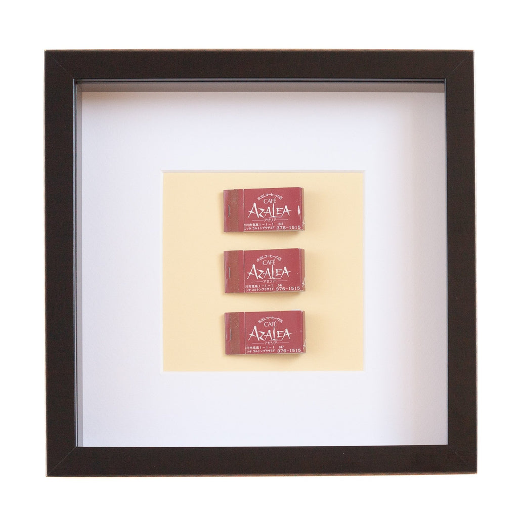 three japanese vintage red matchboxes mounted on a pale yellow background all framed
