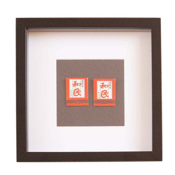 two red japanese vintage match boxes mounted on a grey background in a picture frame