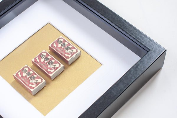 detail of three japanese vintage red matchboxes mounted on a gold background all framed