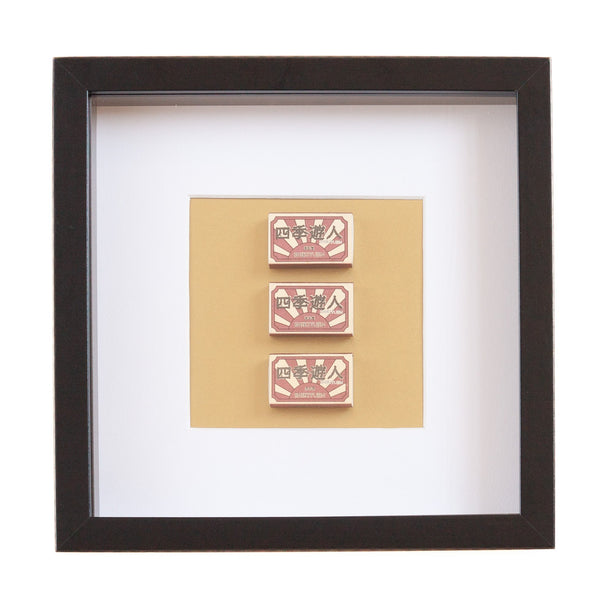 three japanese vintage red matchboxes mounted on a gold background all framed