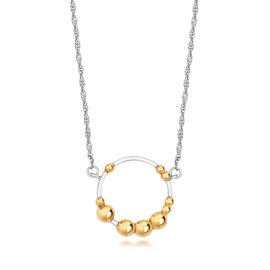 silver chain with a silver hoop pendant with gold dots attached to it