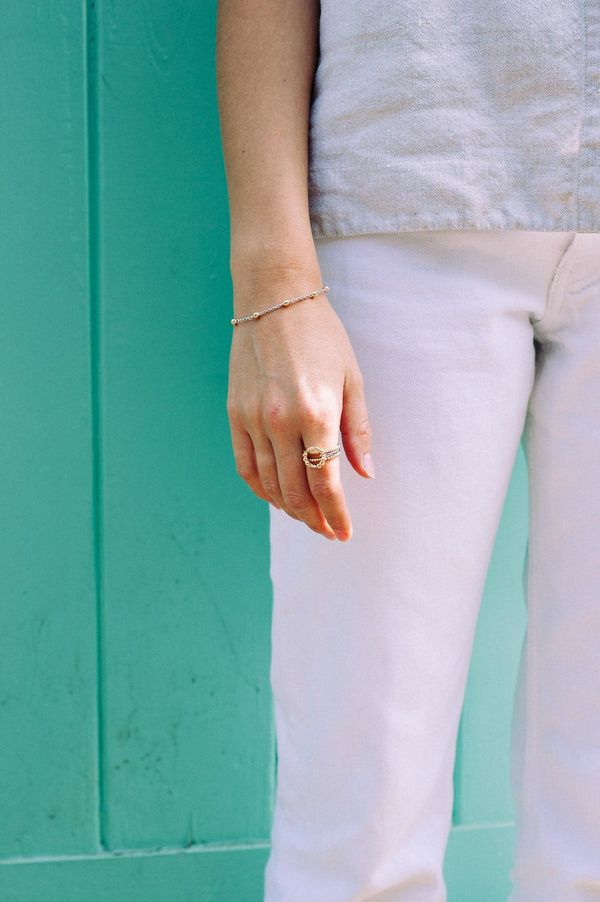 model wearing white jeans and white top and two gold rings made up of lots of little gold dots a gold bracklet