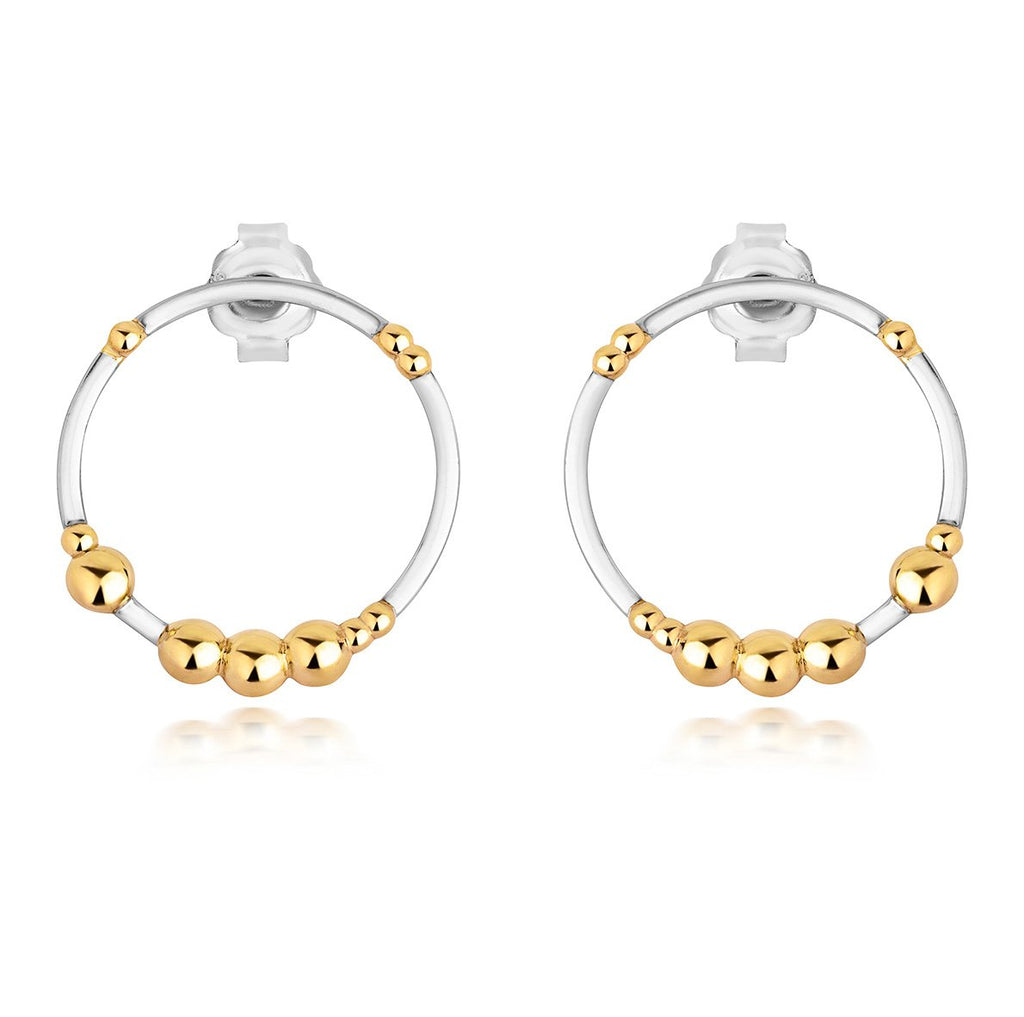 two silver hoop earrings with gold dots on them