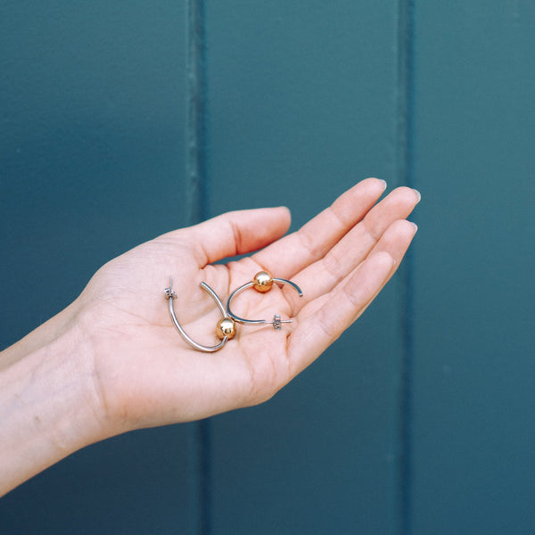 a models hand holding two large silver hoop earrings with one gold dot at the bottom of the hoop