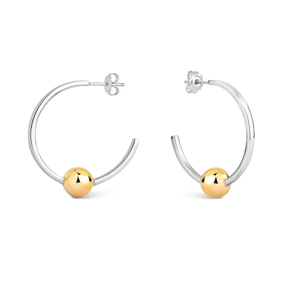large silver hoop earrings with one gold dot at the bottom of the hoop