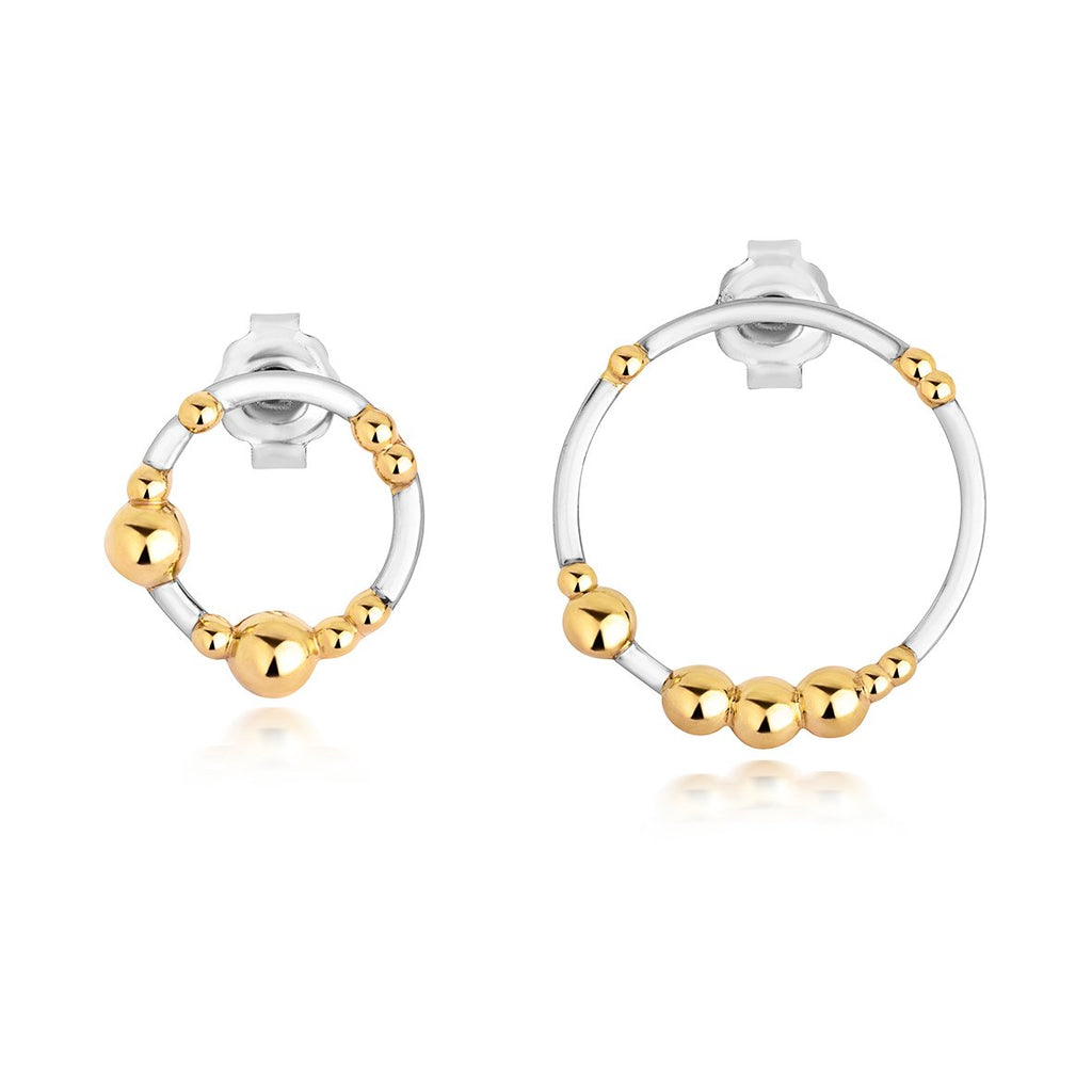 one large silver hoop earring with gold dots on it and one small silver hoop earrign with gold dots on it