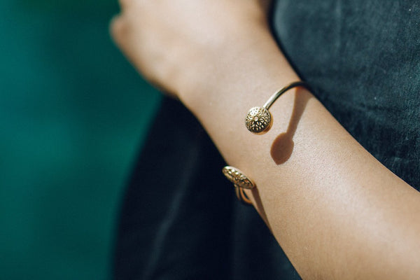 models arm with a gold bangle on it against a black top