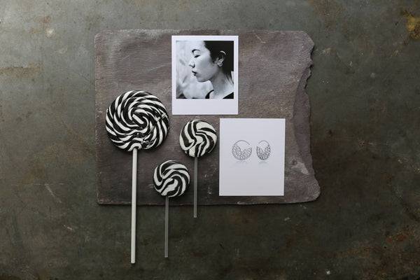 flatlay of some black and white lollipops and polaroids of silver hoop earrings and a female model wearing hoop earrings