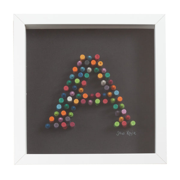 black framed picture of the letter A spelt out in crayons