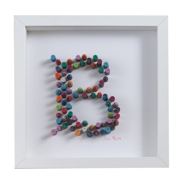 white framed picture of the letter B spelt out in crayons