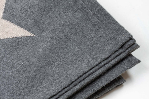 detail of a large grey cotton blanket with a silver star detail