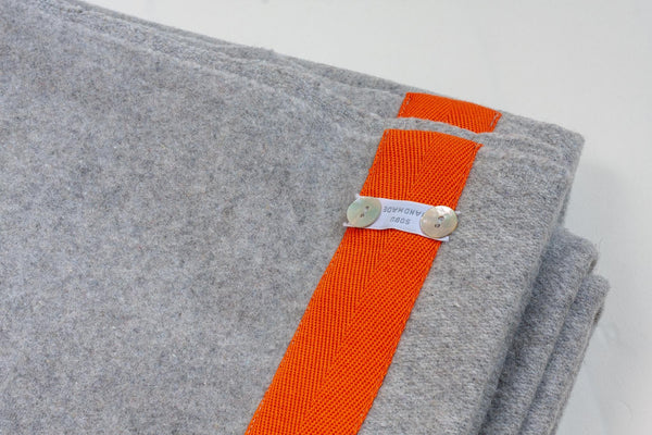 light grey wool blanket with an edging of orange sewn along it