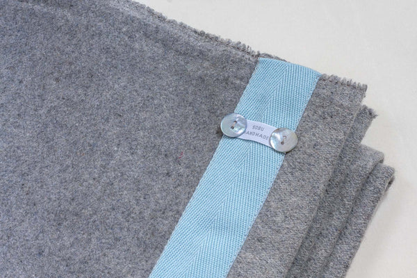 light grey wool blanket with an edging of pale blue sewn along it