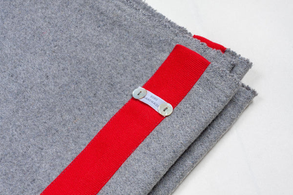light grey wool blanket with an edging of red sewn along it