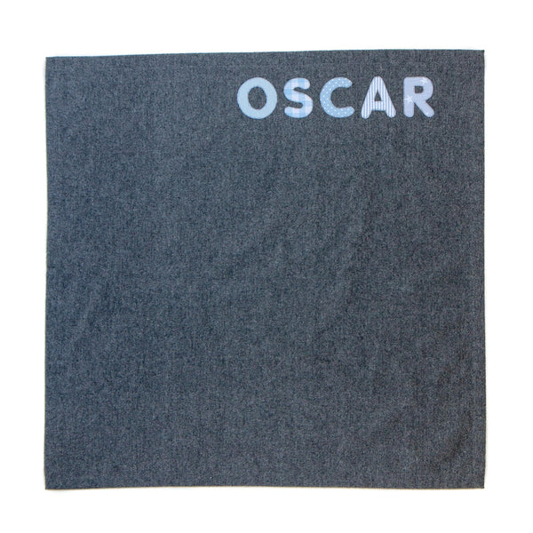 small grey personalised blanket for a baby with the name Oscar sewn in pink into it