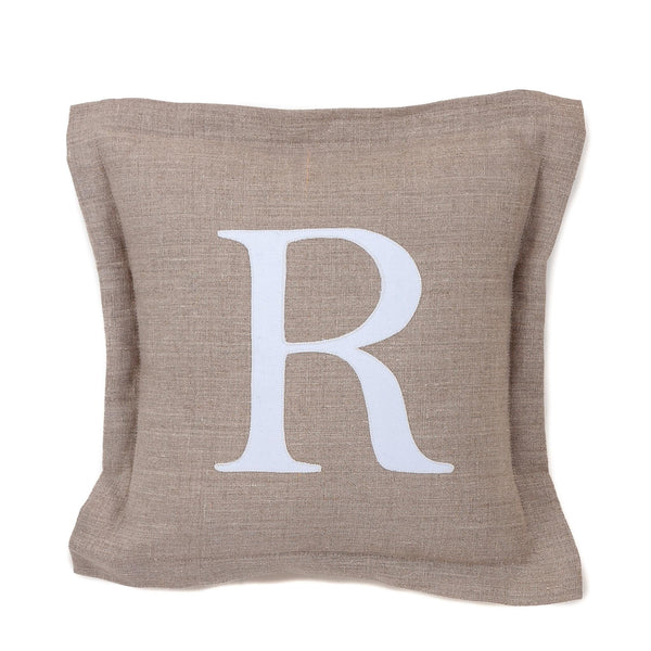 a natural stone coloured linen cushion with the white letter R sewn into the middle of it