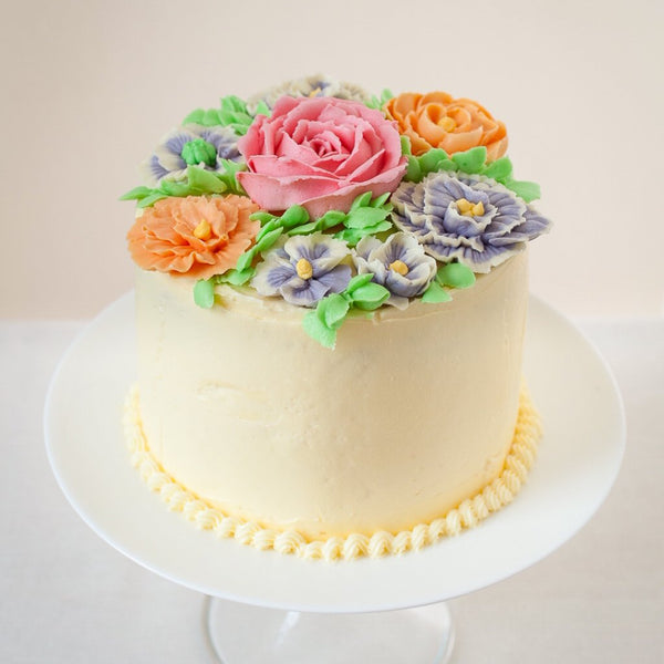 buttercream cake decorated with colourful icing flowers