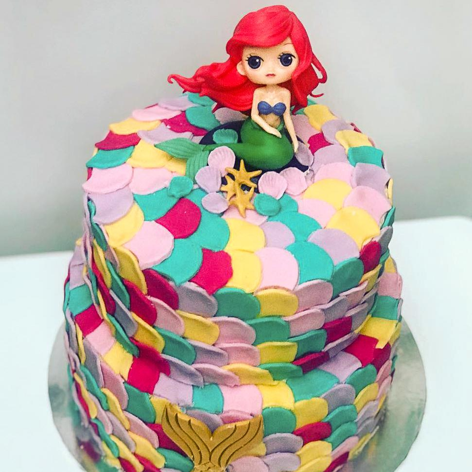 two tiered mermaid character cake covered in colourful shells made from icing and a mermaid decoration
