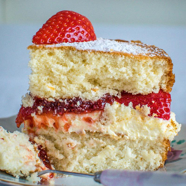 victoria sponge cake dusted with sugar and decorated with strawberries