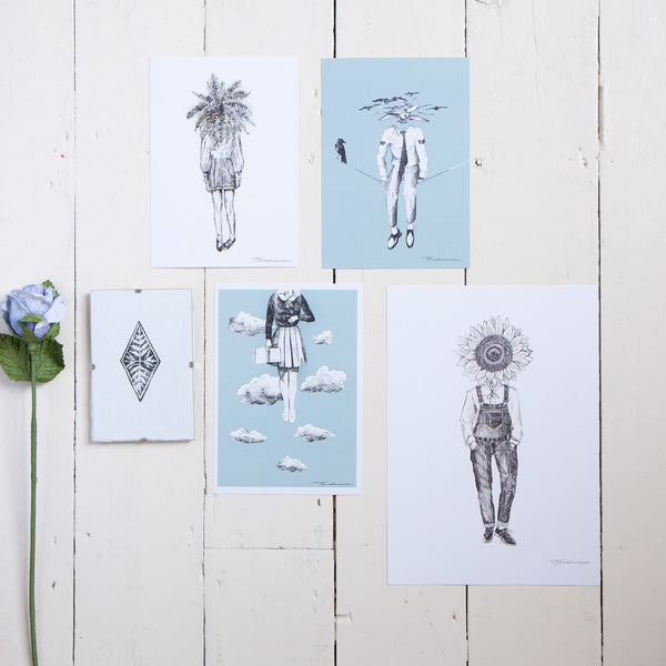 flatlay of different prints with blues whites and black colours including a lino print of a diamond by thea leaney