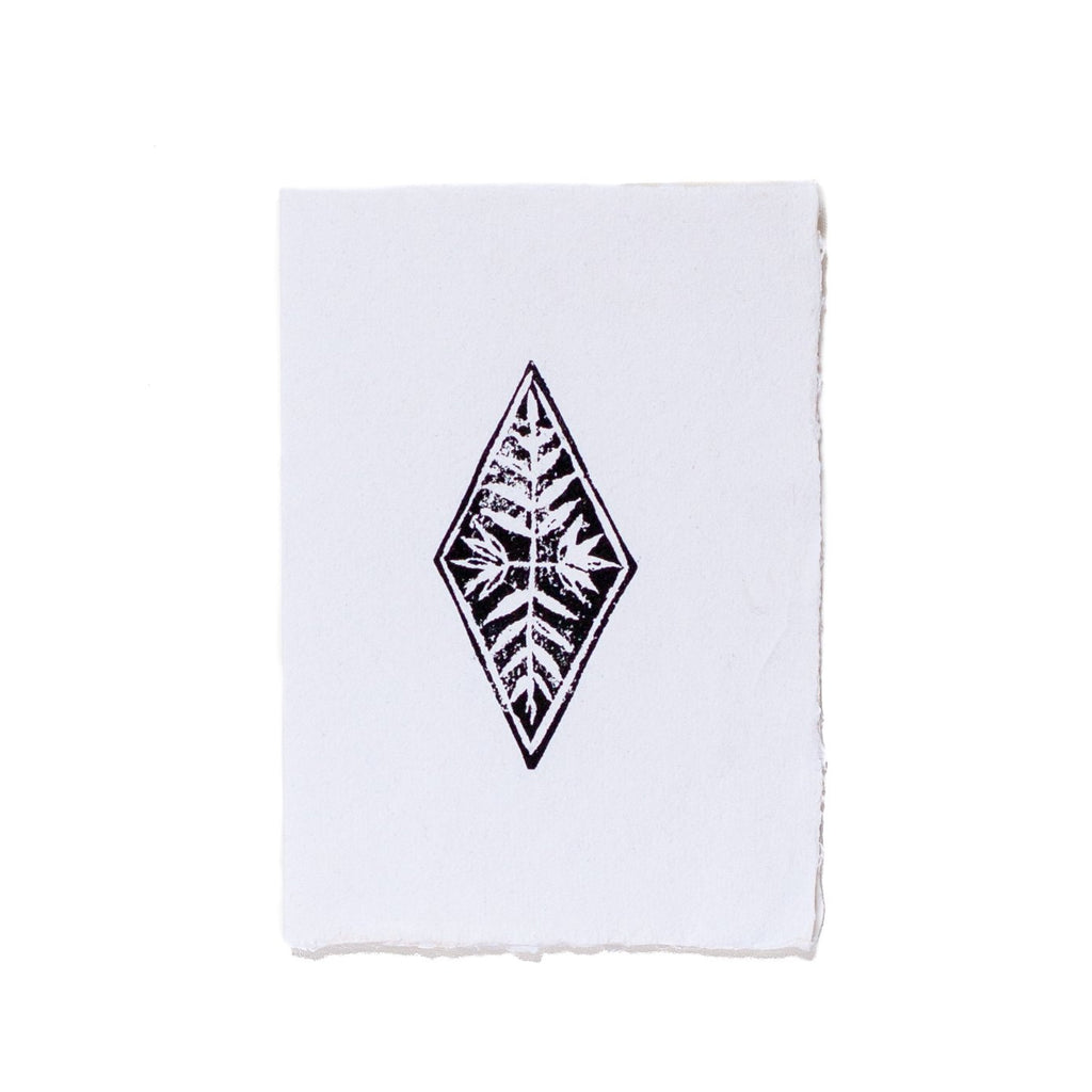 black lino print of a diamond shape printed on white paper