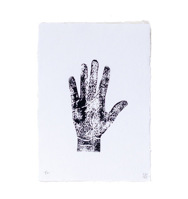 artwork lino print of a hand on a white piece of paper