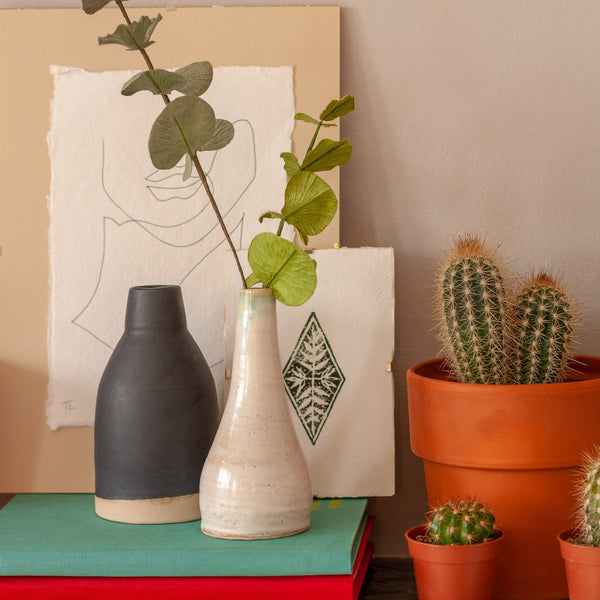 thea leaney prints of a lino printed diamond and a hand drawing picture of a face amonst other objects such as vases and cactus plants propped up on a mantel piece