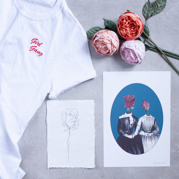 a flatlay of different rose objects including prints flowers and a tshirt