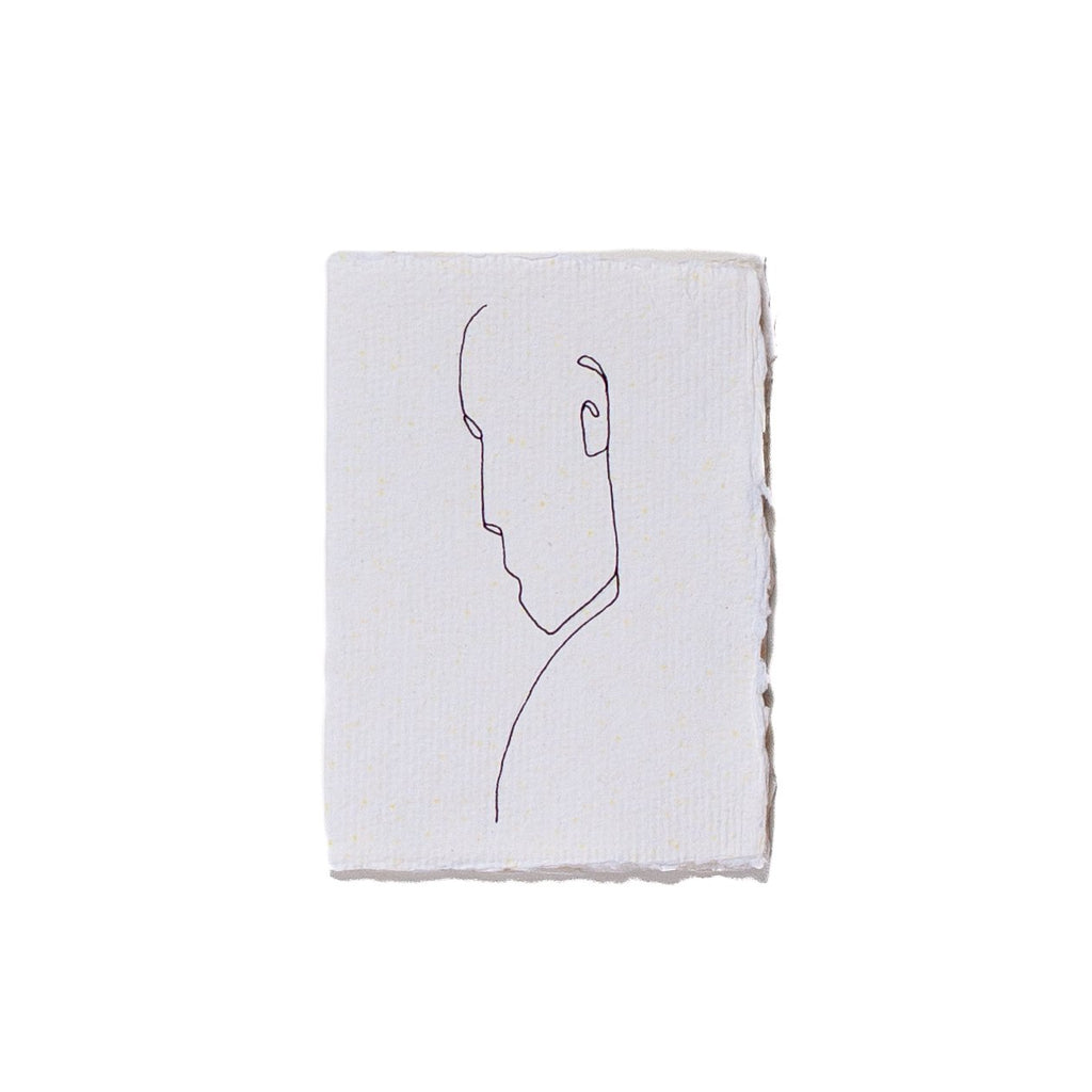 white coloured greeting card with a black outline of a mans face drawn on it