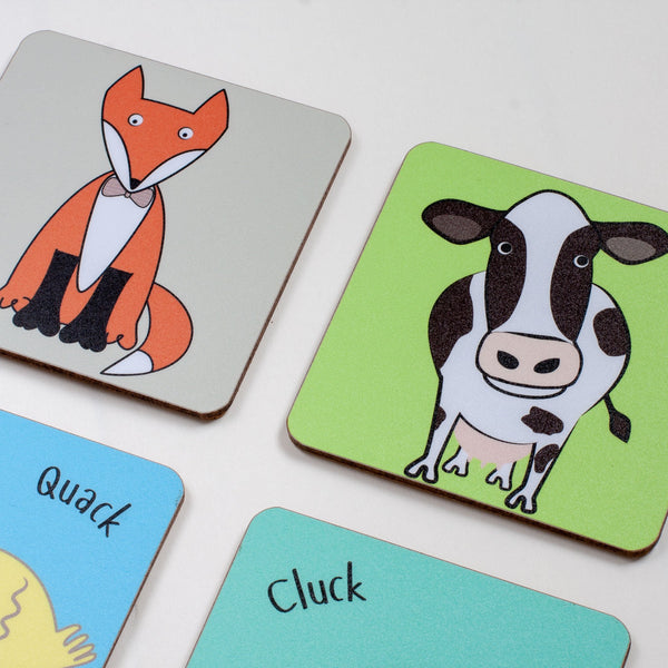 set of four childrens dining table coasters with different animals printed on them including a duck fox cow and chicken