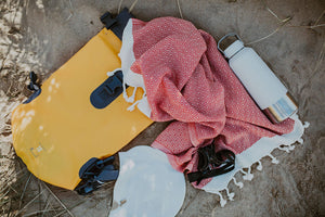 Some open water swimming kit laying on the sand. In this swim kit is a yellow dry bag, a white swimming cap, a white stainless steel water bottle, a pair of black swim goggles and a burnt orange fast drying hair towel from Arc Lore
