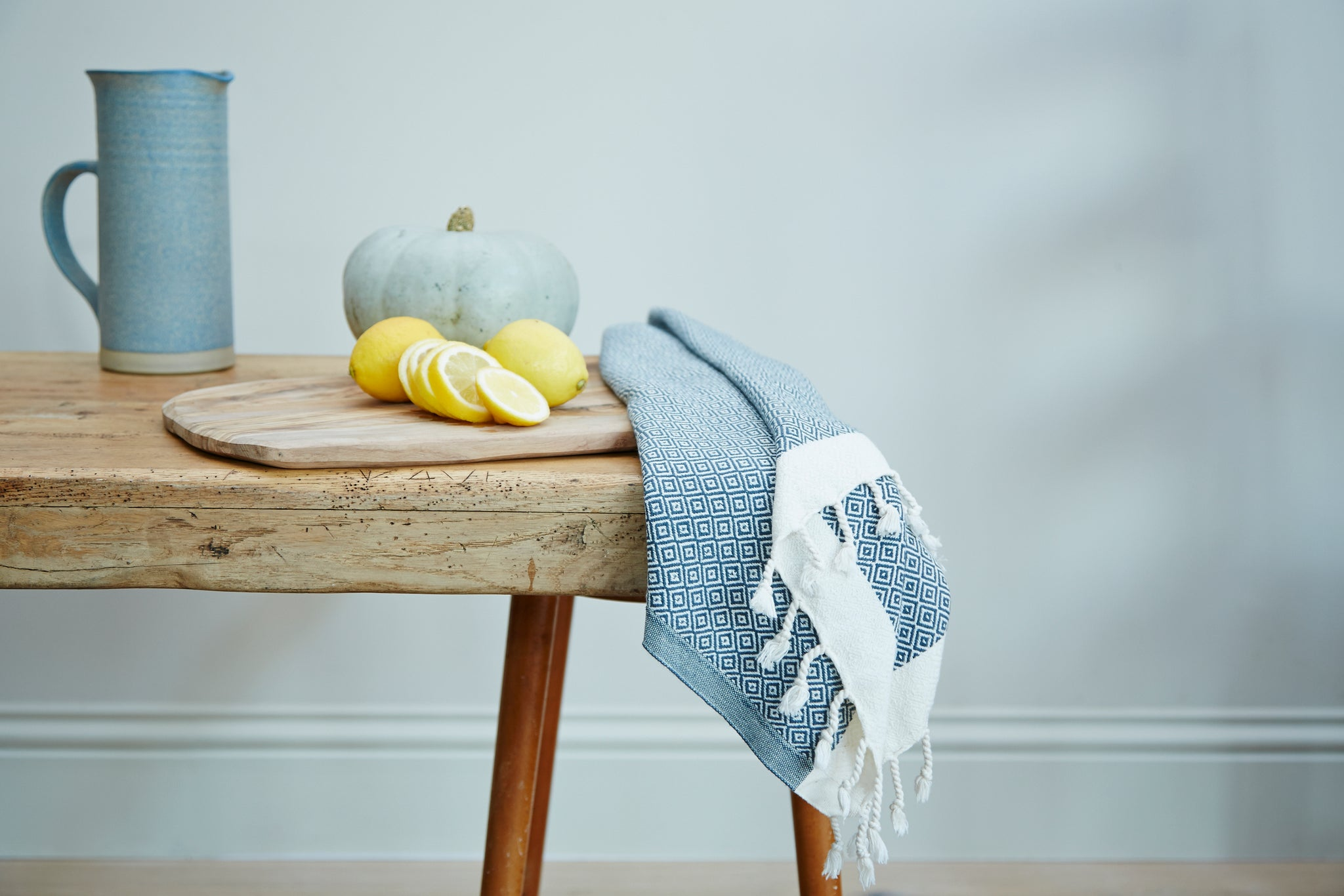 Samimi mini organic cotton towel on a beach wood dining table next to sliced lemons and a jug of water