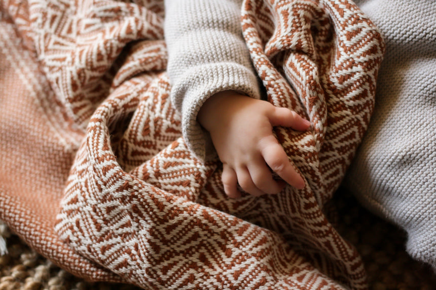 The Loku organic travel throw in the colour brown in use as a baby blanket around a newborn